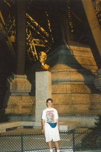 "Posing for a picture at night underneath the beautifully lit up ""Tour Eiffel"" with the master, Mr. Eiffel himself.  Clearly, I dressed up for the occasion with my shorts and my fancy fanny pack (gasp).  I guess fashion wasn't really my strong suit back in the day... (no pun intended!)"
